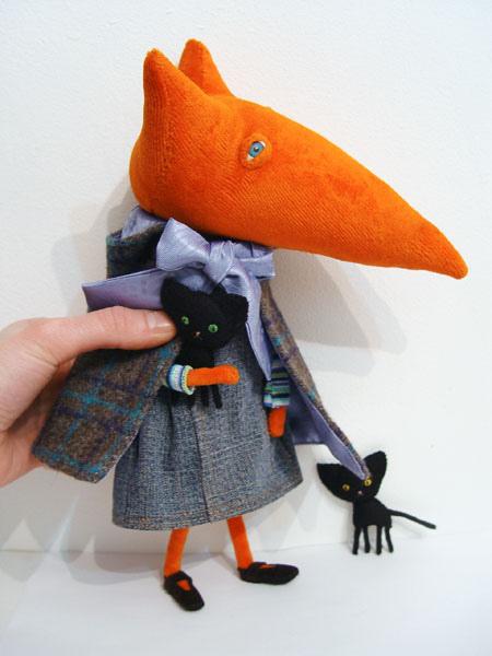 Muñeco de tela con forma de zorro, con ropa y otros detalles.